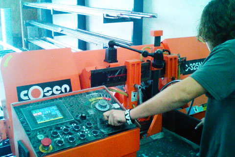 AK Machining specialist operating a saw